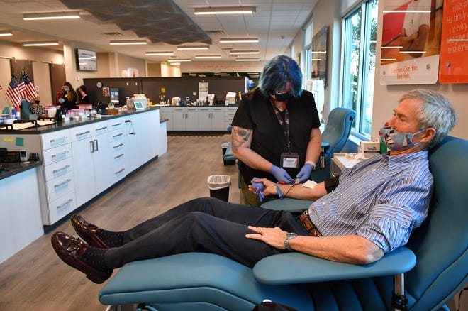 Phlebotomist Jenn Dauthtry accepts a whole blood donation from Tom Crawford on Wednesday morning at Sun Coast Blood Centers' new headquarters in Lakewood Ranch. Crawford, who was a guest speaker at the ribbon-cutting ceremony that morning, credits the blood donor screening process for saving his life.