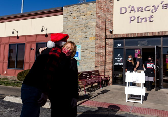 Nicolas Paz, owner of Aztca Mexican Grill, gets a hug from D'Arcy's Pint owner Hallie Pierceall after he picked up a donation of meals from her restaurant to help feed those in need, Wednesday, December 9, 2020, in Springfield, Ill. Paz worked with D'Arcy's Pint, Keefner's, Chadito's Mexican American Grill, along with Johnson and Johnson Auto Service Center and Cherry Hills Church to provide over 130 meals to families from the restaurant's food truck set up outside Johnson and Johnson's parking lot. [Justin L. Fowler/The State Journal-Register]
