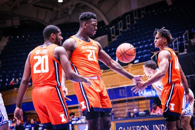Kofi Cockburn (21), Da'Monte Williams (20), Adam Miller (44) share a handshake during the University of Illinois' men's basketball victory over Duke on Tuesday in Durham, N.C.