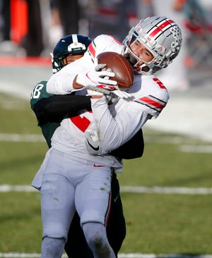 Ohio State receiver Chris Olave, right, catches a touchdown pass in the end zone against Michigan State's Kalon Gervin during the second half of an NCAA college football game, Saturday, Dec. 5, 2020, in East Lansing, Mich.