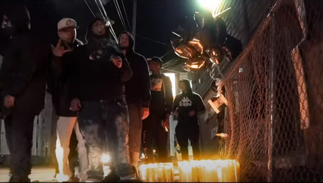 "In this still image taken from a video, Juan ""King Pun"" Figueroa  raps next to a memorial for 17-year-old Paul Collazo-Ruiz, who was shot and killed in October 2019 of Ashley Boulevard and Tallman Street ."