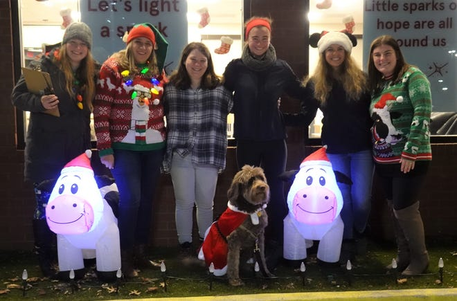 The lighting crew at Chick-fil-A in Jackson Township for the restaurant's inaugural holiday light display. From left, supervisors Michaela Mushett and Chelsea Swanson, team member Natalie Pugh, service director Lexi Fricker with her dog Lola, marketing director Melanie Farmer and supervisor Abby Nussbaum.