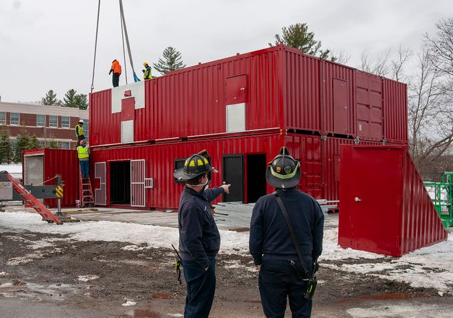 Auburn Firefighters watch as a new training facility is assembled Wednesday.