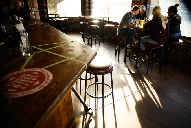 A group of women have drinks at Carolina Ale House on Wednesday, Dec. 9, 2020, in Fayetteville. Starting on Friday, non-essential businesses like gyms, restaurants and retail will have to close at 10 p.m. nightly.