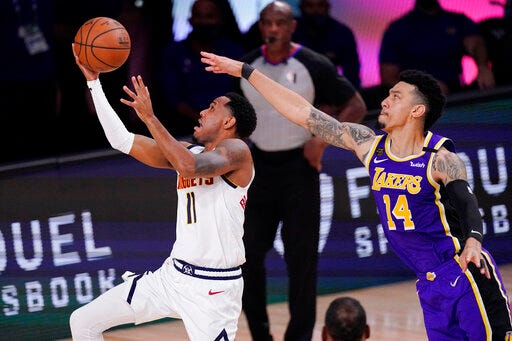 Denver Nuggets guard Monte Morris, left, drives ahead of Los Angeles Lakers' Danny Green during the second half of an NBA conference final playoff basketball game on Sept. 26 in Lake Buena Vista, Fla. (AP Photo/Mark TerrillJ