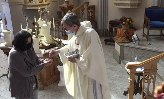 Pueblo Bishop Stephen Berg hands the blessed sacrament to a parishioner at the Cathedral of the Sacred Heart during an online Mass in November.