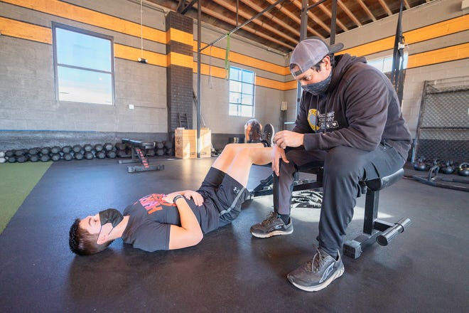 Tony Harrison, owner of Colorado Movement Company, right, helps Ryan Lane work on diaphragmatic breathing techniques on December 9, 2020.