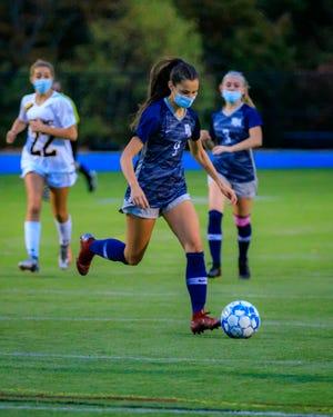 Kylee Slavik mantiene su ojo en la pelota mientras la lleva por el campo. [Wicked Local Photo/E. Gene Chambers]