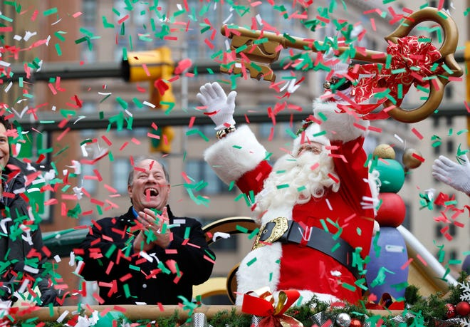 Santa Claus gets the key to the city from Detroit Mayor Mike Duggan during the 92nd America's Thanksgiving Day Parade on Woodward Avenue in Detroit on Nov. 22, 2018.