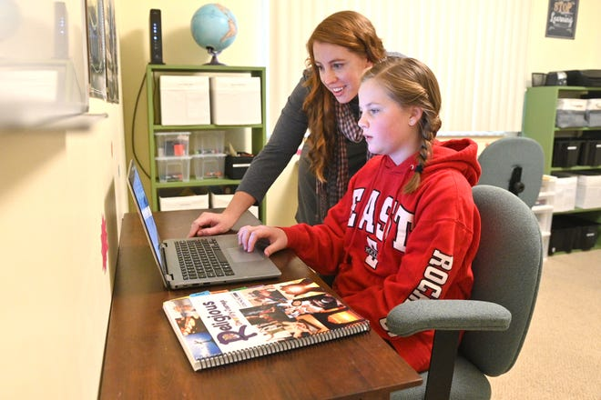 Kennedy Clawson works at her home school desk with her mother Rachel Clawson as they work on Religious Diversity Journeys, part of The Interfaith Leadership Council, a local group responsible for the course, at their Canton home on Tuesday, December 8, 2020.