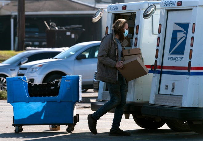 A rural carrier assistant loads packages into a mail truck at the United States Post Office in Henderson, Ky., Tuesday afternoon, Dec. 9, 2020.
