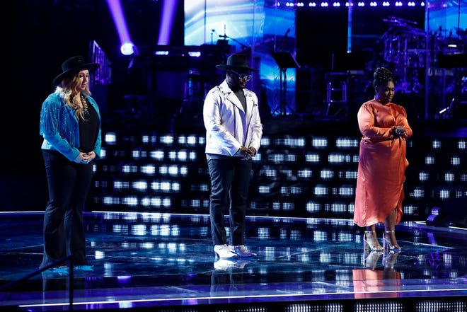 "John Holiday, middle, awaits the Top 9 results live on ""The Voice"" Tuesday night with Bailey Rae, left, and Tamara Jade. The voice professor at Lawrence University in Appleton is moving on to the finals."