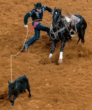 Miles City's Haven Meged moves toward his calf to establish a new go-round record of 6.8 seconds in tie-down roping during Round 6 of the National Finals Rodeo Tuesday at Globe Life Field.