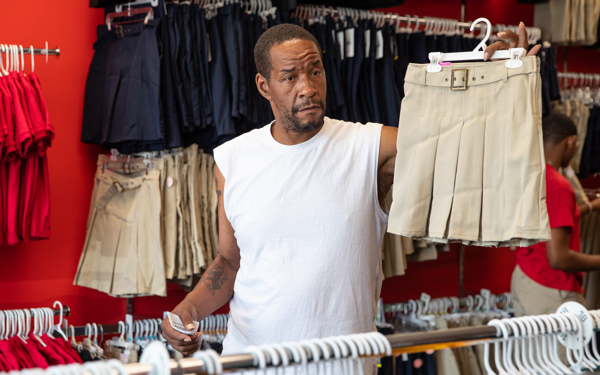 """Kevin Rhodes Sr. holds up a skirt to get his daughter Ke'Asia's opinion while shopping for school uniforms at School Zone on Wednesday, July 24, 2019. """"You like this one, momma?"""" he asked. """"Or, you want a dark color?"""" Ke'Asia would pick the light color skirt. """"I cook, clean, everything. I do the whole works,"""" said Rhodes Sr. """"It's kind of rough but I can handle it though."""""""