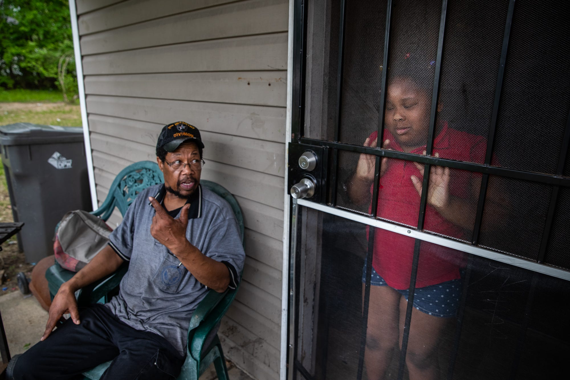 """Robert O'Neil tells his daughter, Mary, 8, to go over to the church parking lot across from their home to pick up the toys she and her three siblings took over. """"This is my day, Monday through Sunday,"""" he said. """"Come home (from work), come in the house, make dinner, do bed, go to work."""" O'Neil, a veteran, works as a third-shift custodian at the Richard Roudebush VA Medical Center to provide for his family. O'Neil says he sleeps two to three hours a day and credits his military background for keeping him going."""