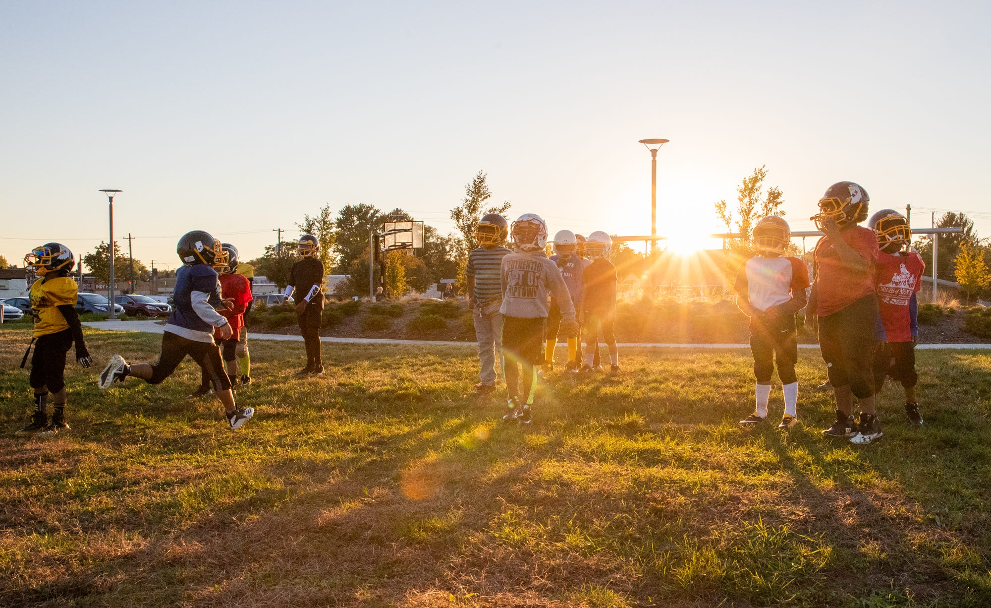 """The Indy Steelers practice as the sun sets at Tarkington Park, where the team's practice field is located, in Indianapolis. """"Tarkington side, you can go right around the corner and it'll be shootings, robberies, you'll hear police sirens,"""" said Donnell Hamilton, who grew up in the Butler-Tarkington neighborhood and founded the Indy Steelers 15-years ago. """"It's a bit more of a struggling side. Some people wouldn't understand what some of these kids are going through. Some people are really hungry out here. It's a lot going on out here, it's a lot."""" Former Indy Steeler player Jay Roberts, who now plays for a local high school team, says the program needs to stay around as long as it can. """"They're not just at home bored, they're not seeing what's going on in their environment,"""" he said. """"They get a chance to take two hours out of their lives to have fun."""""""
