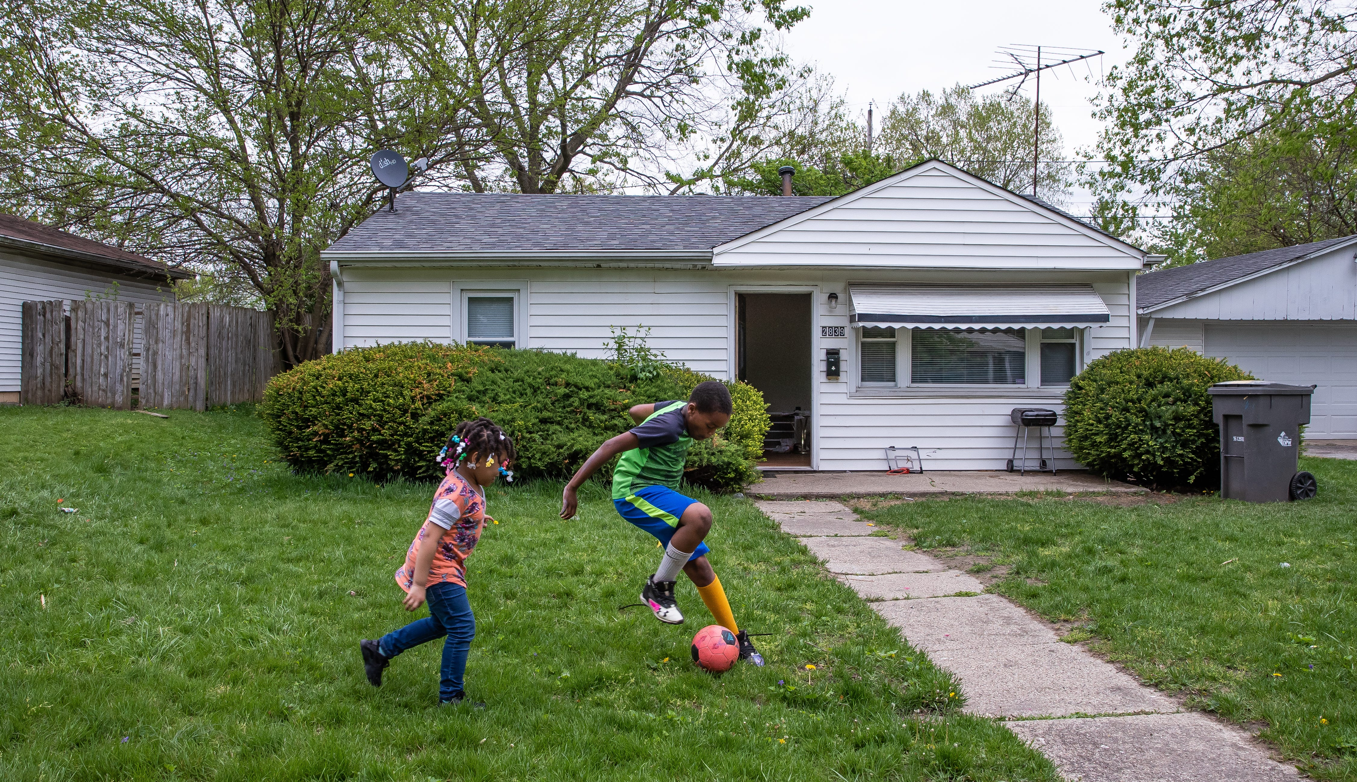 """Kevin Rhodes Jr., an Indy Steelers football player, plays soccer with his cousin at his new home in Indianapolis on Wednesday, May 1, 2019. Rhodes Jr.'s father, Kevin Sr., moved him and his sister, Ke'Asia, to the new home after multiple robberies at their home on Herschell Avenue in Indianapolis. """"Our house got broken into when I was out trick-or-treating with my kids,"""" said Kevin Sr. """"They came in Ke'Asia's window so she wouldn't sleep in her room anymore."""" Kevin Sr. raises his two children alone. The children would see their birth mother, Jannie, almost every day before her death."""