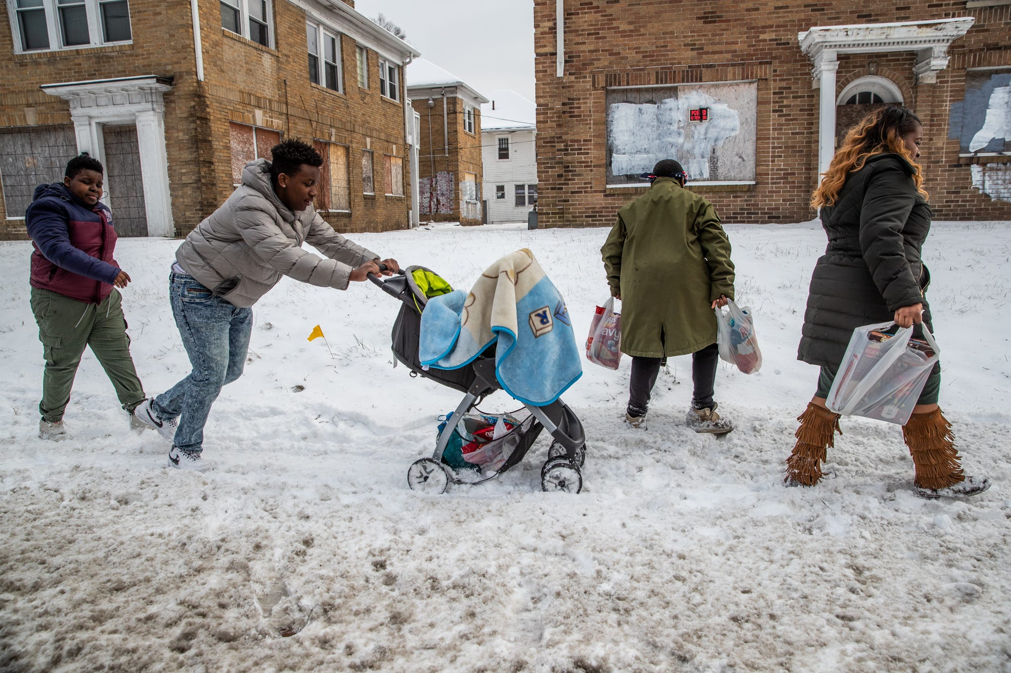 """Takkara Delaney (right) walks on an uncleared sidewalk along 38th Street in Indianapolis with her children Friday, Feb. 1, 2019, after shopping for Super Bowl party food at Family Dollar for a party she's throwing for her sons. Dai Reid, 14, (middle left) who Delaney adopted, and Tyree Delaney (left) struggle to push Tytus Delaney, 10 months, in the stroller. """"The boys are always helpful,"""" said Takkara. """"They go above and beyond to make sure I'm OK when it should be the other way around. Their hearts are so big."""" Tyler Delaney, 11, carries two bags filled with the family's favorite snacking chips. Three of Delaney's boys play for the Indy Steelers."""
