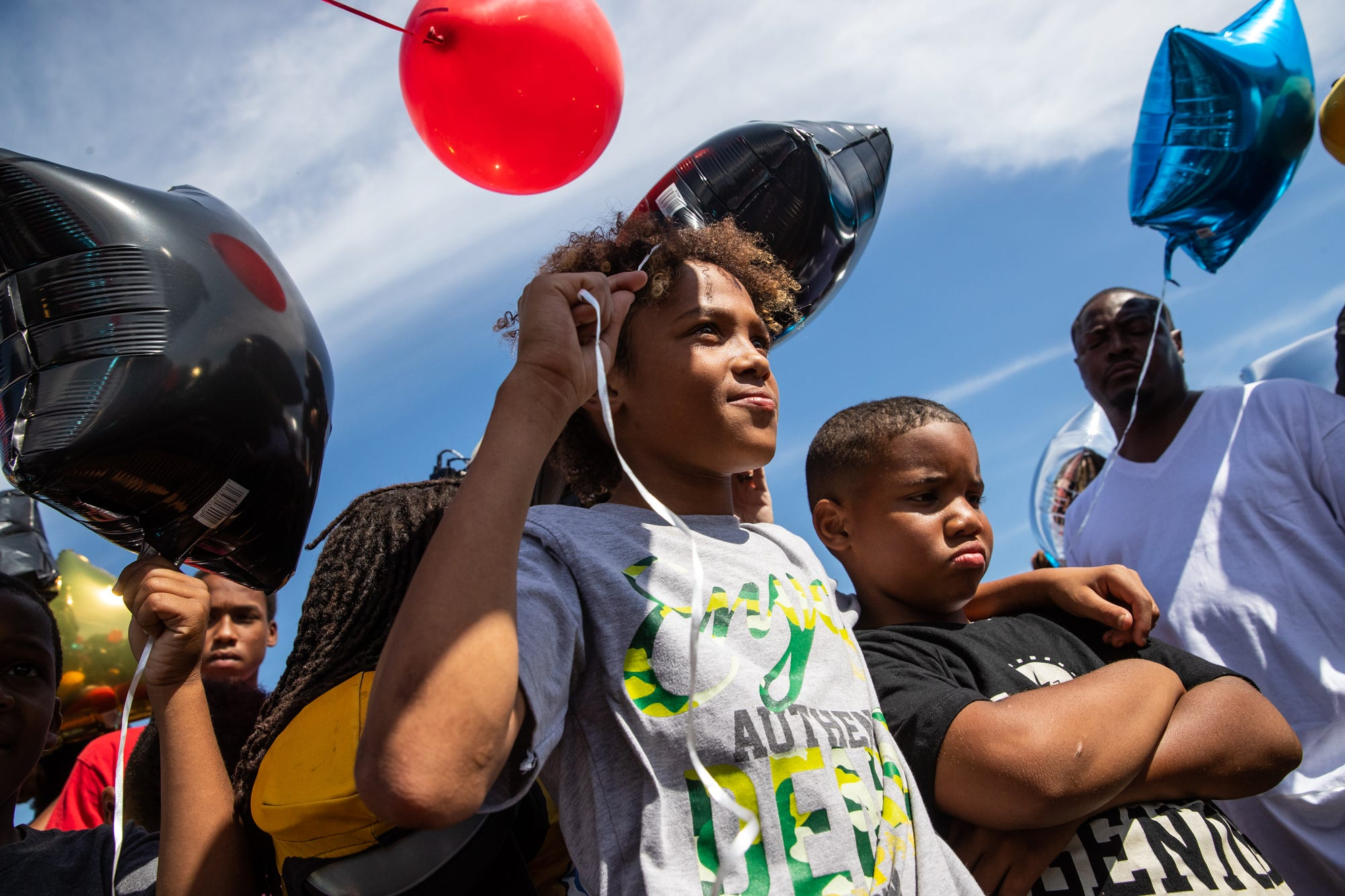 """Cam Harden holds a balloon and listens as family and friends remember former Indy Steelers football player DeShaun Swanson during a balloon release in his honor at Watkins Park on Sunday, Sept. 22, 2019. Swanson, 10, was murdered in a drive-by shooting in the Butler-Tarkington neighborhood in 2015, not far from the team's practice field. The case remains unsolved. """"I definitely miss him every day,"""" said coach Donnell Hamilton. """"He was probably the littlest guy on the field with the biggest heart. He played for two years and the year that happened was in September and it crushed us."""" The team gathers yearly to honor Swanson with a balloon release and football games. """"His memory certainly lives on. Each of the kids there has a story about him or a story about his life and you realize with DeShaun, right down the street from the park, that's a reality for these kids and that's what I think normalizes it. They see that stuff, what is the solution?"""""""