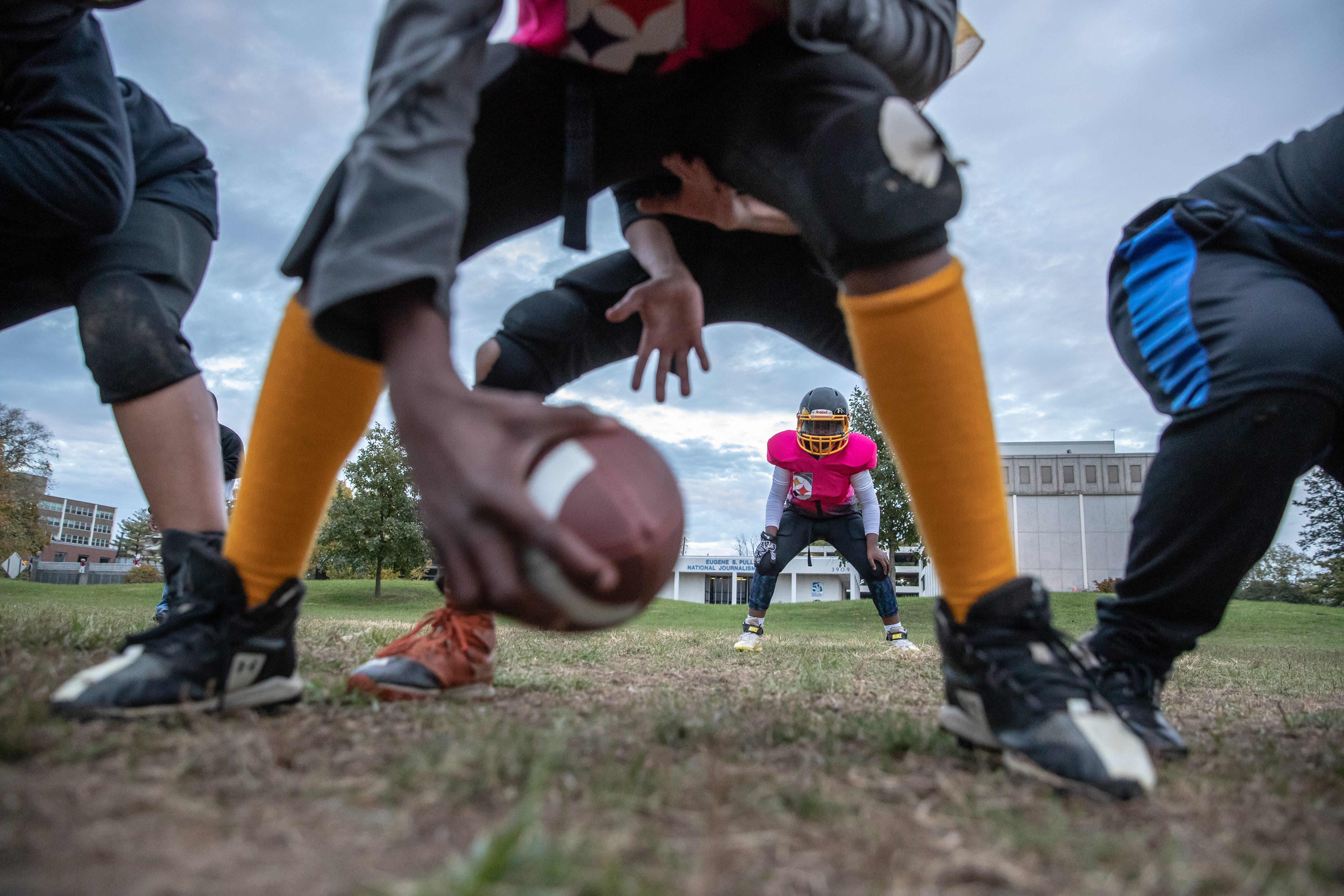 """Indy Steelers 10u running back Chloe Williams, known to her teammates as the First Lady and is the first female football player in the 15-year history of the Steelers, prepares to take the handoff during practice at Tarkington Park. The park, located just off Illinois and 38th Street, is typically busy with hundreds of people on summer nights. And though the kids are playing football to stay out of trouble, according to Lacie Nix, mother of two Steelers players, """"sometimes the trouble finds them."""" During a practice at Tarkington Park gunshots rang out. """"When you hear gunshots your natural reaction is to run, so trying to explain to an 8 or 9-year-old kid, it's like we don't want you to run you have to get down. It's not something that you want to explain to a kid,"""" said coach Donnell Hamilton. Nix remembers asking kids if they were OK after the incident. """"Several of them looked at me and said, 'Oh, that's normal,'"""" said Nix, """"That's not normal. That shouldn't be normal for them."""""""