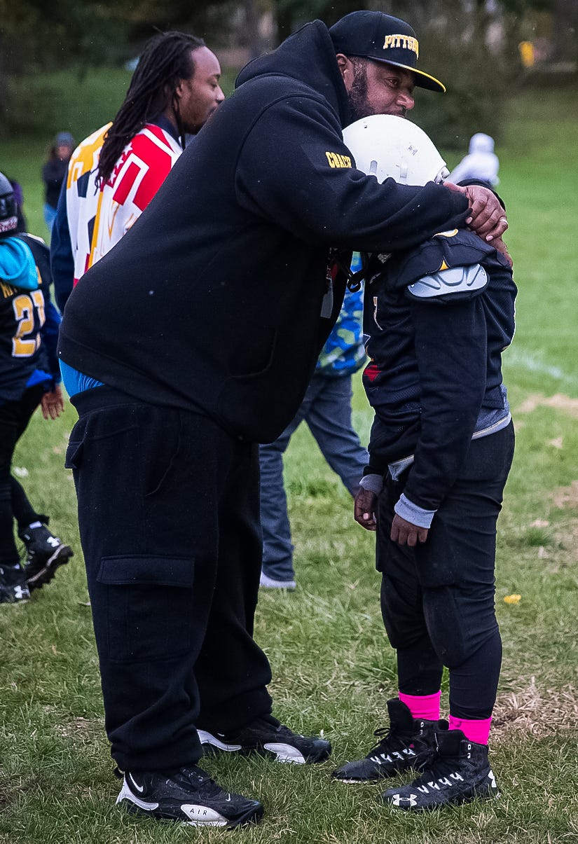 """Coach Donnell Hamilton comforts an Indy Steelers player after an 8u team loss at Frederick Douglass Park. """"I didn't know when I was in college that I would be a coach,"""" he said. """"I think I'm a very passionate coach, I want to teach them everything I know. That's what drives me."""""""