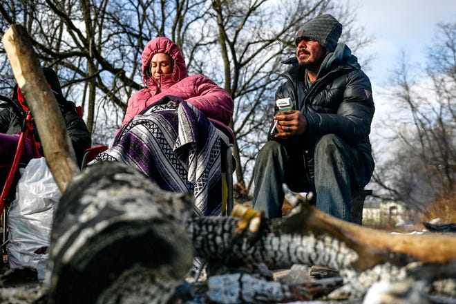 William File and Heather Vincent warm themselves by a fire at a homeless encampment on Wednesday, Dec. 9, 2020, in Lansing.
