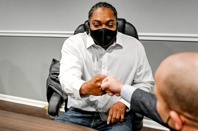 Herbert Alford, left, fist bumps attorney Jamie White on Wednesday, Dec. 9, 2020, at the White Law office in Okemos. Ingham County Prosecutor Carol Siemon dropped a murder charge against Alford on Tuesday.