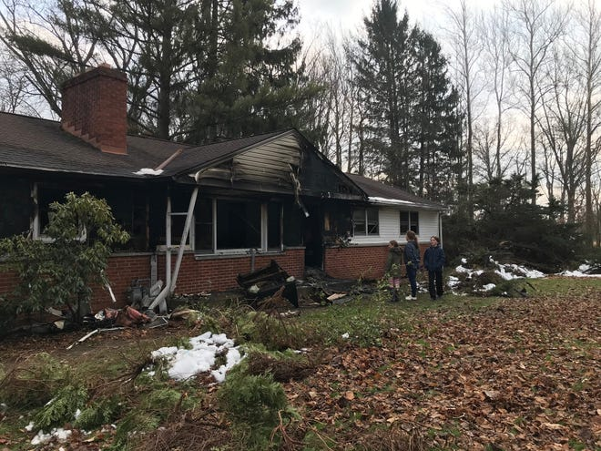 A fire at the home of Michael Lewis and his fiance Tonya McGlasson Wednesday morning heavily damaged the house and its contents. Three of the children look over the fire damage Wednesday.