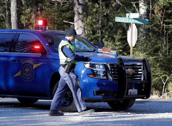 A Michigan state trooper walks to his squad car blocking the road at Gooseneck Lake Drive in Hiawatha National Forest on Wednesday, Dec. 9, 2020.  A Wisconsin Air National Guard fighter jet crashed Dec. 8 in the forest in Michigan's Upper Peninsula.