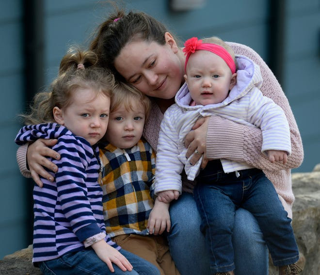 Callie Clark, 28, with her children Peyton Rinehart, 4, left, Cain Rinehart, 2, and Ella Jo Rinehart, 7 months, in front of her apartment on Tuesday, December 8, 2020, in Nashville, Tenn. Clark is at risk of getting evicted after recently losing her job. She received some aid to help her from the Metro Action Commission.