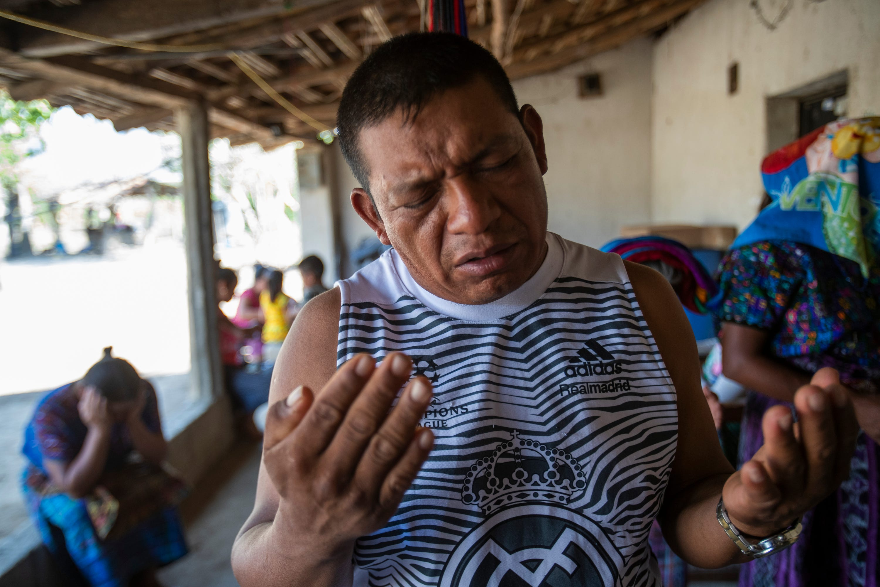 Francisco Sical prays for his father's health as members of his community gather for a moment of prayer in early March 2020.