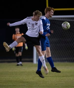 Tate High School's Caleb Wise (No. 11) fights for control of the ball against Washinton Hgh School's Trevor Shaffer o. 29) during the battle of unbeaten teams on Tuesday, Dec. 8, 2020.