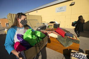 Phoenix resident Lisa Altenbernd carries hygiene kits she assembled for men and woman experiencing homelessness at the Central Arizona Shelter Services in Phoenix on Dec. 9, 2020.