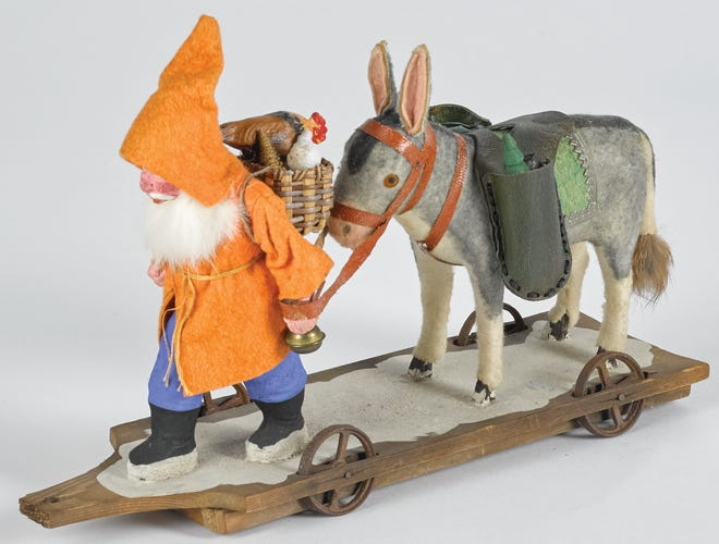 This hardworking Santa in an orange and blue outfit is carrying toys with a donkey not a reindeer. The 8-inch toy was made in Germany.