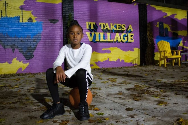 London Riley poses for a portrait in front of an I Promise Village mural in Akron, Ohio, in October 2020.