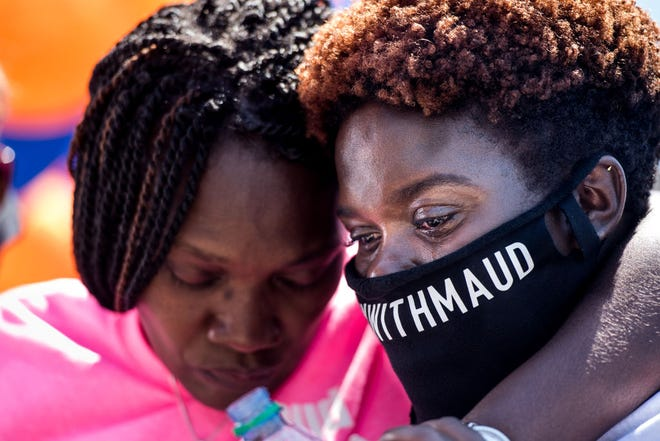 Jasmine Arbery, sister of Ahmaud Arbery (R) and Wanda Cooper-Jones, Ahmaud's mother, comfort one another while people gather to honor Ahmaud at Sidney Lanier Park on May 9, 2020 in Brunswick, Georgia. Arbery was shot and killed while jogging in the nearby Satilla Shores neighborhood on February 23.