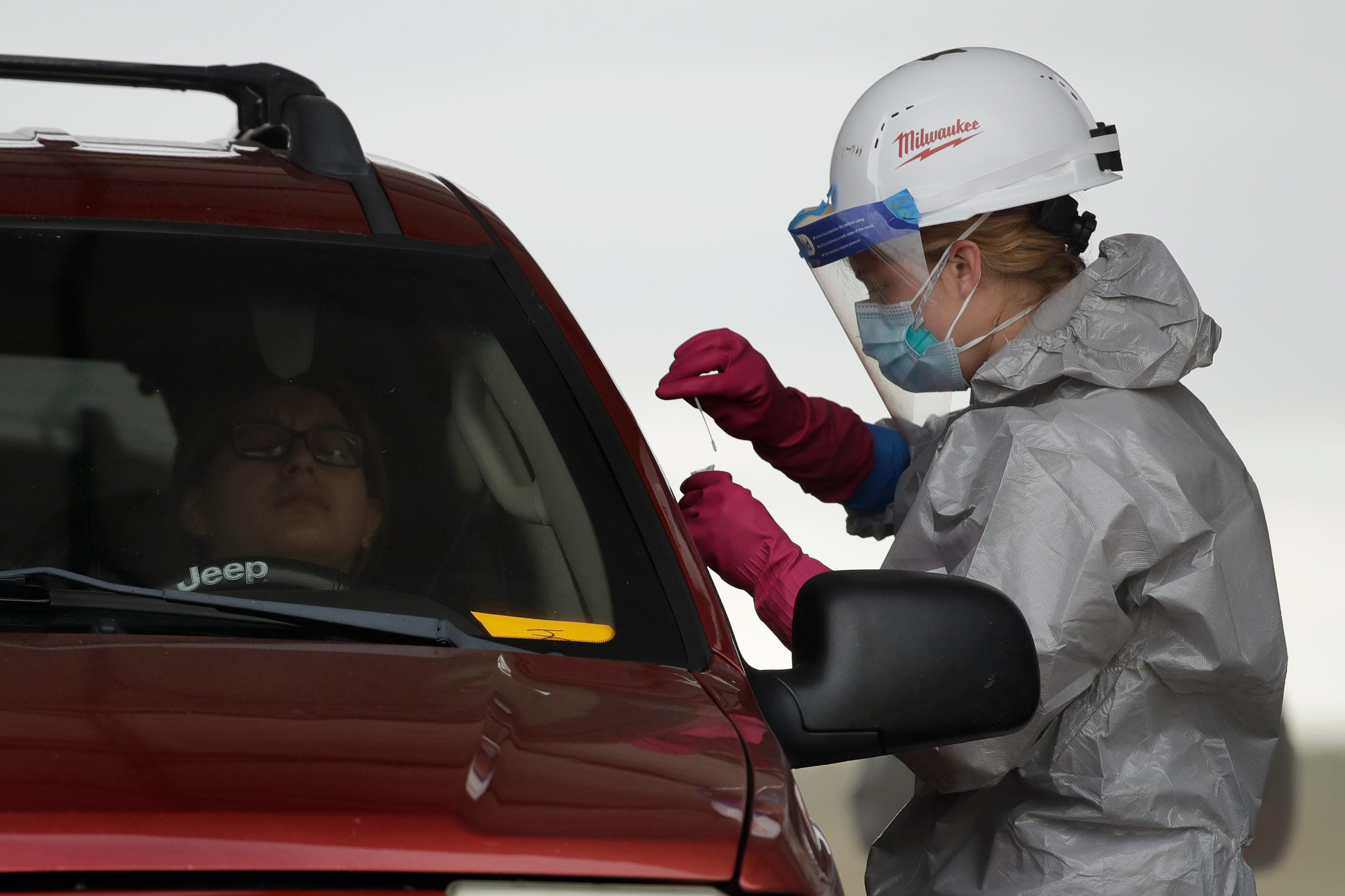 Kansas National Guard member Jessica Pal collects a sample at a drive-thru COVID-19 testing site May 20 in Dodge City, Kan. Army and Air Force medical guard units have tested 100-200 people daily.