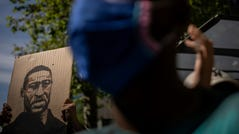 A demonstrator holds a George Floyd placard in front the American embassy in Madrid, Spain, Sunday, June 7, 2020 during a demonstration over the death of George Floyd and victims of racial injustice.