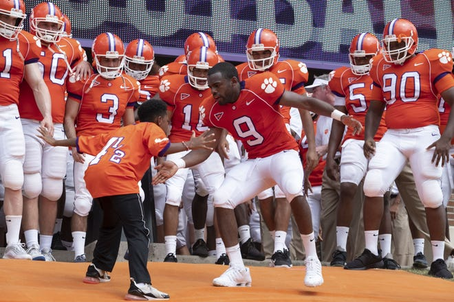 """Ray McElrathbey (Jay Reeves, center right) and his little brother Fahmarr (Thaddeus J. Mixson) get hyped before a Clemson game in the Disney+ sports drama """"Safety."""""""