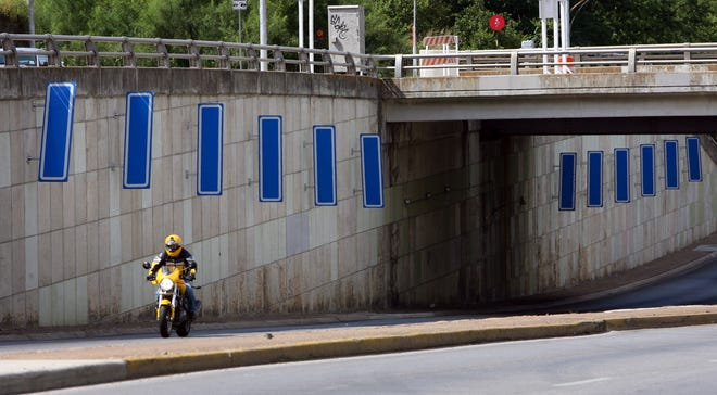 "A motorcyclist travels north on Lamar Boulevard under the Fifth Street overpass, passing the art installation ""Moments"" in 2006. On Thursday, Austin City Council approved the artwork's official removal from the city's public art collection."