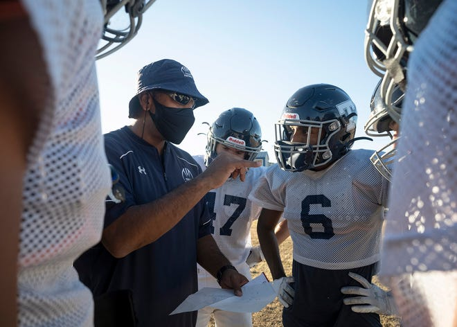 Texas School for the Deaf head coach John Moore Jr., left, signs in the huddle as Kylar Sicoli, center, and Jordan Leeper look on during practice Wednesday. TSD will compete against Veritas Academy in the six-man state championship game Friday in Waco.