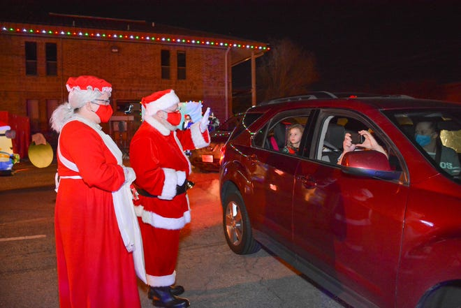 Mr. and Mrs. Claus greet Pflugerville residents Friday night during the Pfestival of Lights drive-thru event.