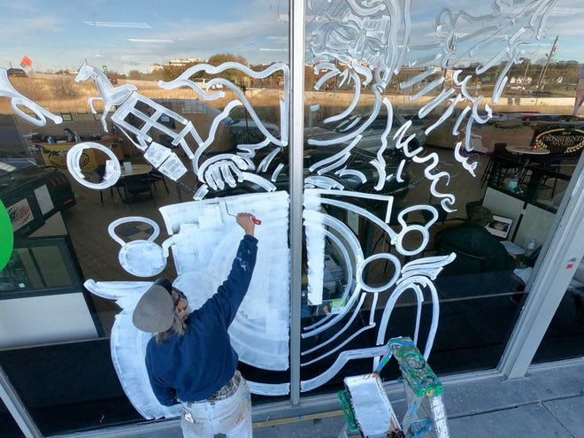 Tom Besson has been painting holiday decorations on local auto dealerships for 40 years.