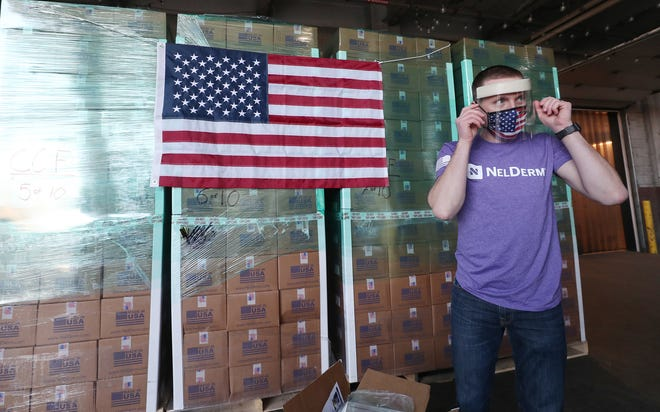 Kevin Nelson, president and founder Nelson Innovations, dons a face shield Thursday on the loading dock of Bounce Innovation Hub in Akron. Nelson's company is donating 100,000 faces shields to the Cleveland Clinic.