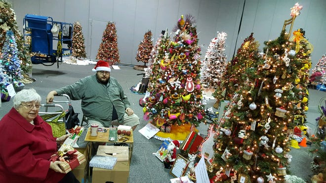 In a photo from about 2018, Mary Ellen Reymann and her son, Keith, decorate a Christmas tree for the Akron Children's Hospital Holiday Tree Festival. Mary Ellen and her husband, Dick, coordinated the delivery of the trees after purchase for 33 years, and Mary Ellen and family decorated trees for about 10 years. Mary Ellen died of COVID-19 on Nov. 20.