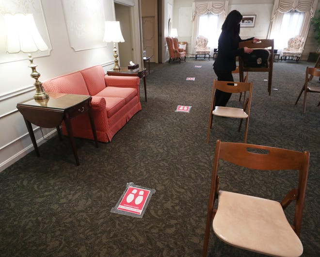 Footprint signs are a reminder to maintain social distance as Kelsey Hofer, funeral director and embalmer, sets up chairs in a chapel at Billow Fairlawn Chapel & Crematory in Fairlawn.