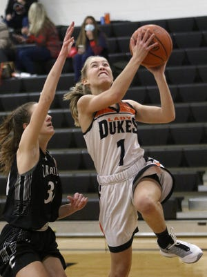 Marlington's Maria Warner, right, going up for a shot defended by Carrollton's Grace Leslie during conference action at Marlington High School on Wednesday, December 9, 2020.