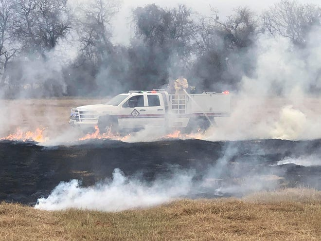 Love County firefighters work to put out a grassfire that was started off Gladney Lake Road, near Highway 77. The suspected cause was a cigarette thrown out by a passing car.
