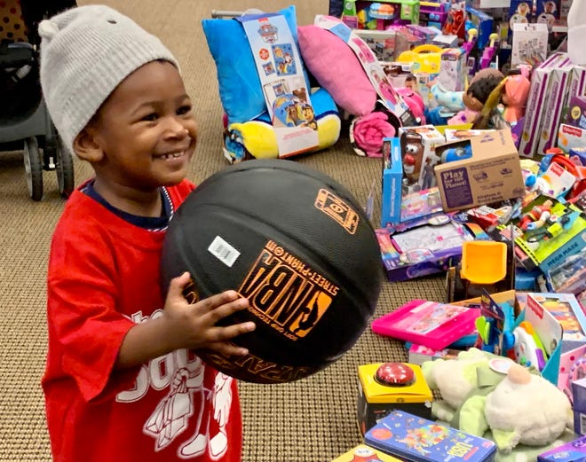 Two-year-old burn patient Jai'kobe Terry picks out a ball he likes during Shop With a Doc at Doctors Hospital on Thursday.