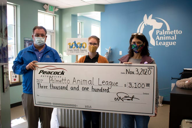 Left to right, Peacock Subaru general manager Ken Kirby, Palmetto Animal League adoptions and intakes coordinator Sally Dawkins, PAL president Amy Campanini.